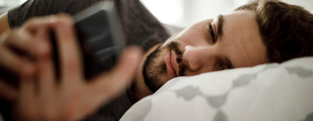 man laying in bed with phone