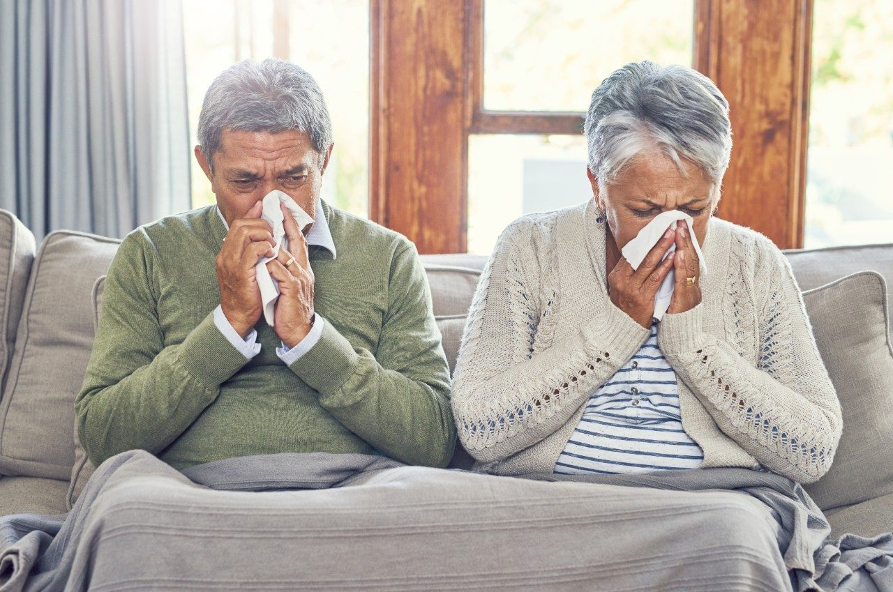 Shot of a sickly senior couple each blowing their nose with a tissue while sitting on a couch at home