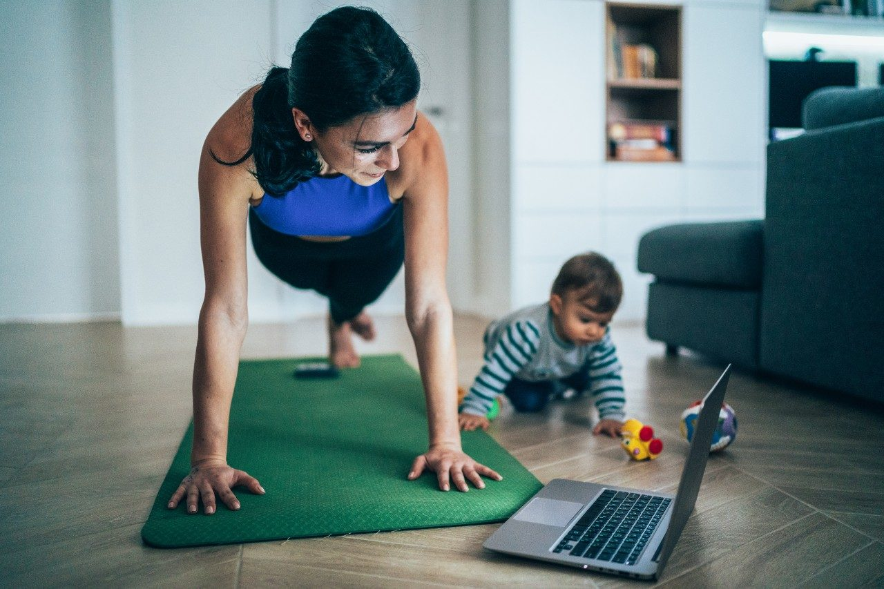 Woman exercises while watching workout video on a laptop and her baby playing around