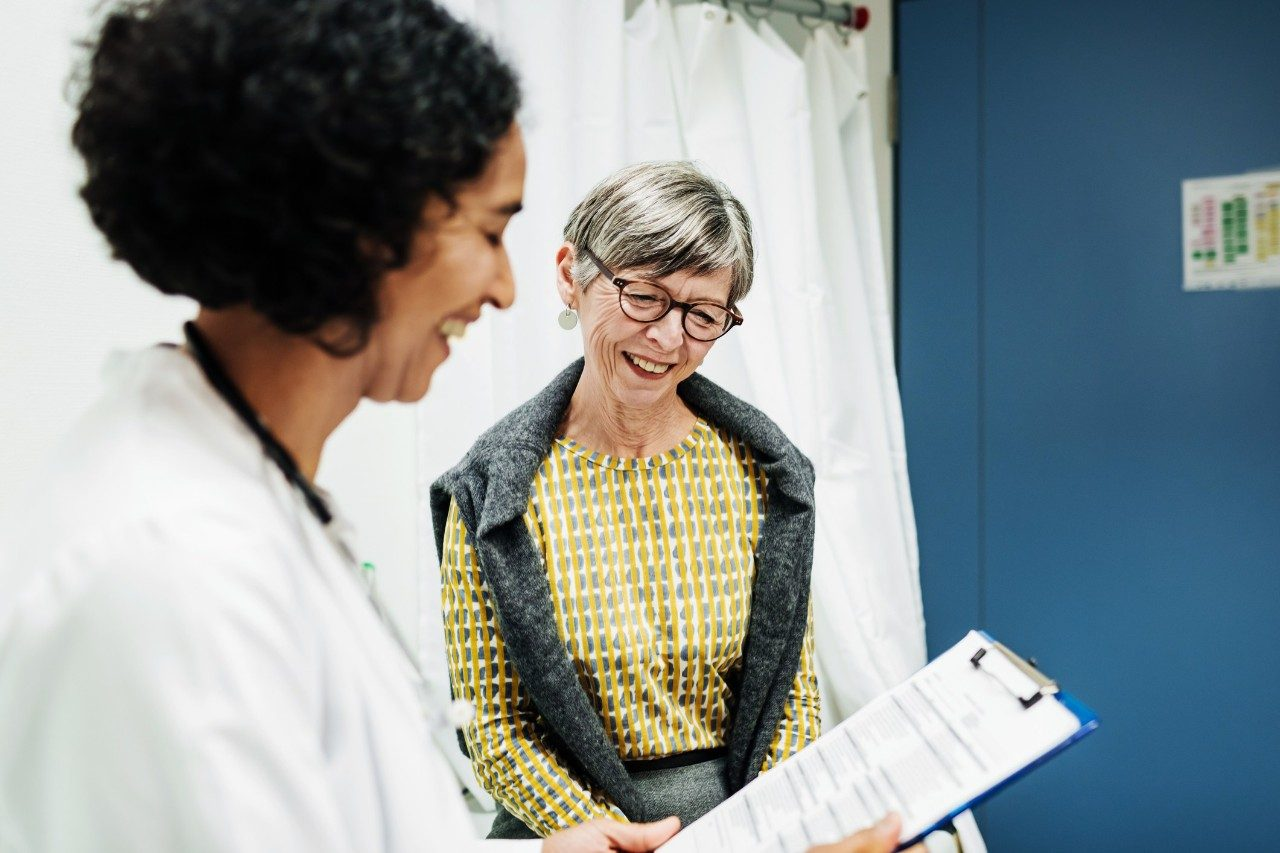 A clinical doctor going over some test results with an elderly patient at the hospital.