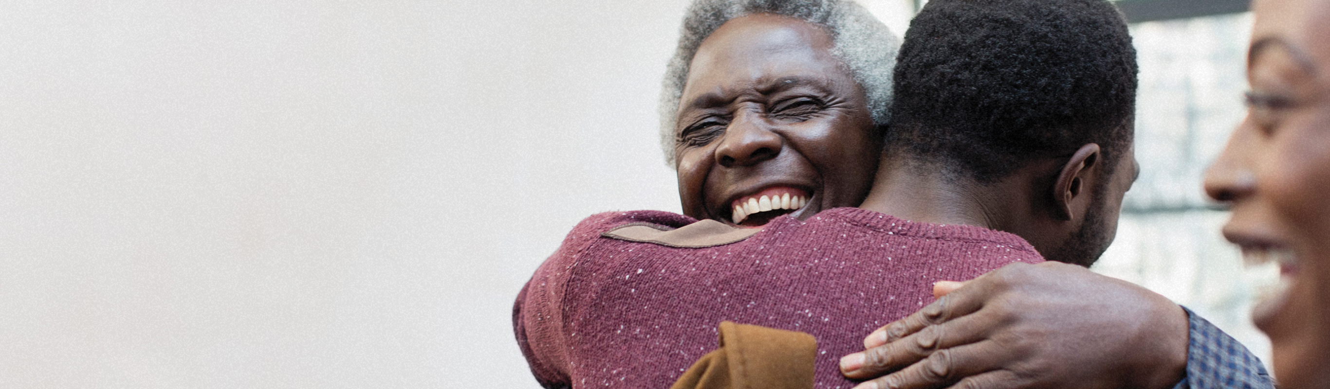 Man with gray hair embracing other man, smiling.