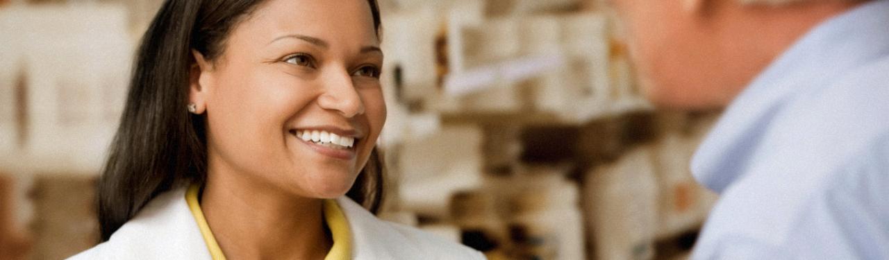 药剂师对着男顾客微笑。