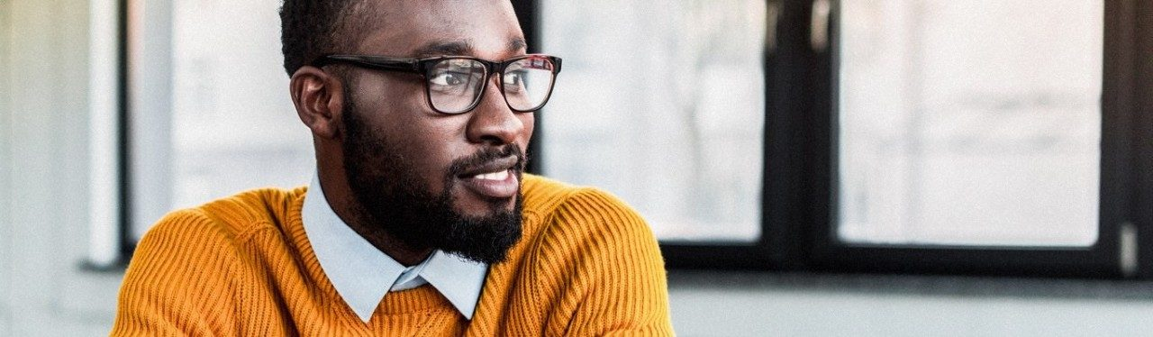 Hombre con barba, con suéter naranja y gafas.