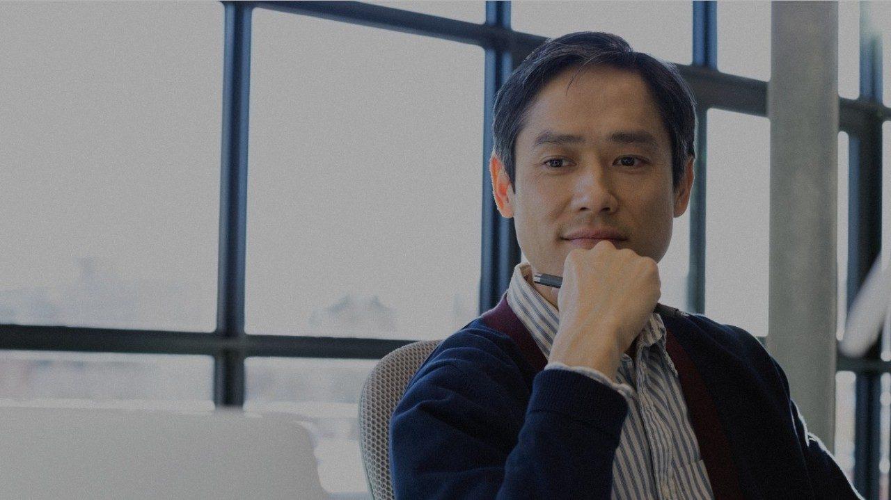 Man holding pen sitting in office.