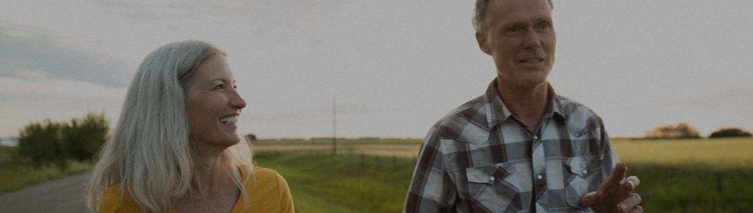 Senior couple walking outside near field.