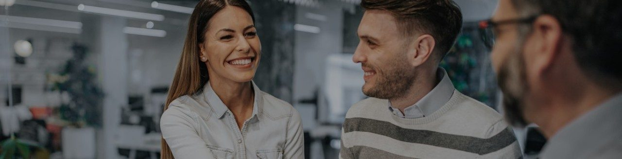 Young man and woman smiling in office talking to man in glasses.