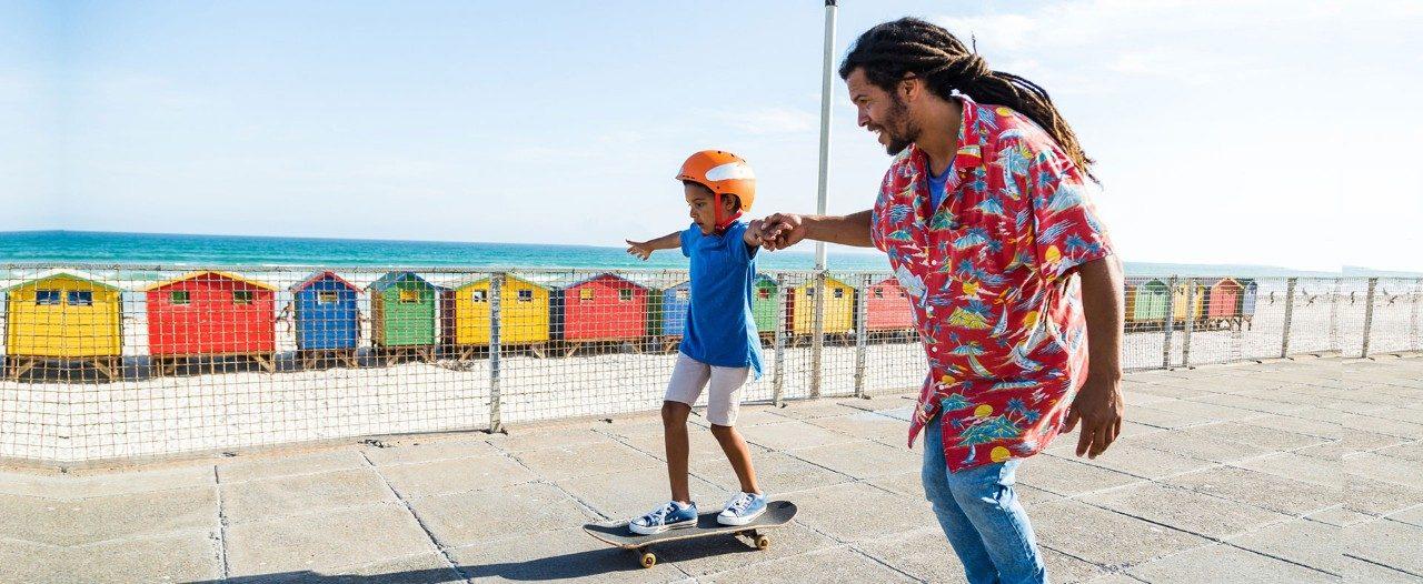 Father teaching son to skateboard on beach boardwalk