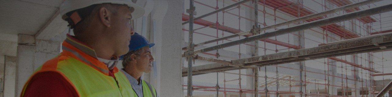 两个戴安全帽的人在看建筑工地。