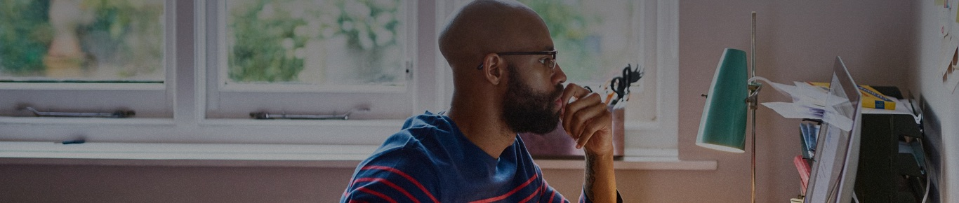 Man with beard and glasses sitting in front of laptop at home.