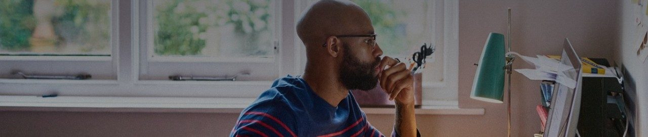 Hombre con barba y gafas sentado frente a la computadora portátil en su hogar.