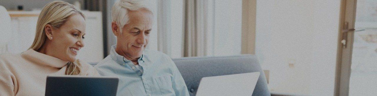 Mujer rubia con una computadora portátil sentada en un sofá junto a un hombre mayor con una computadora portátil.