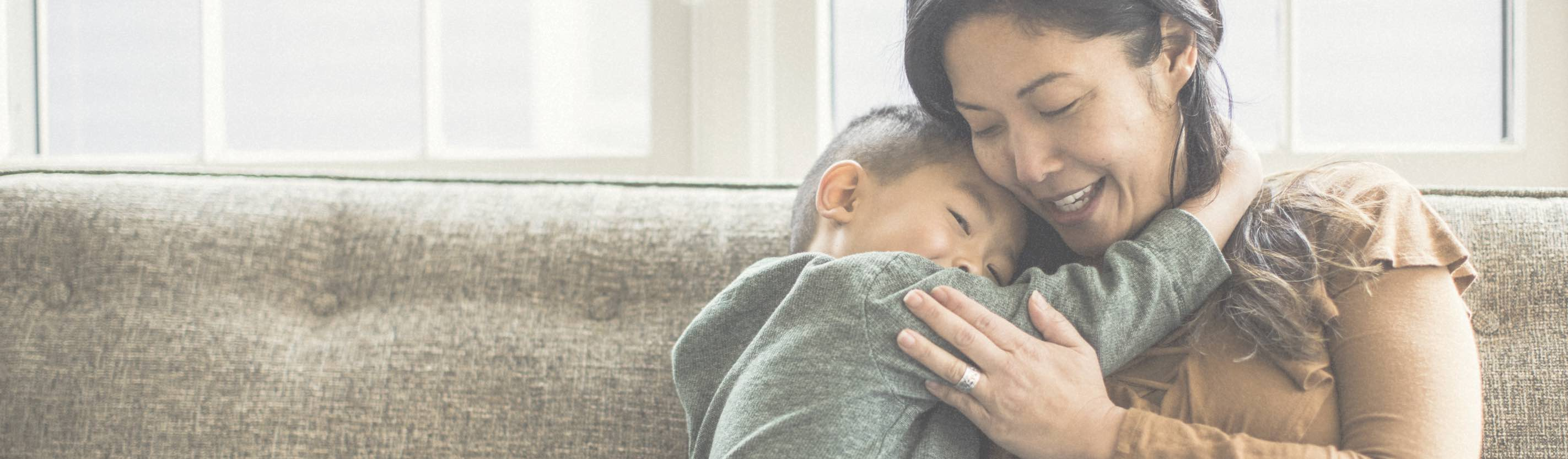 Woman hugging her son on the couch.