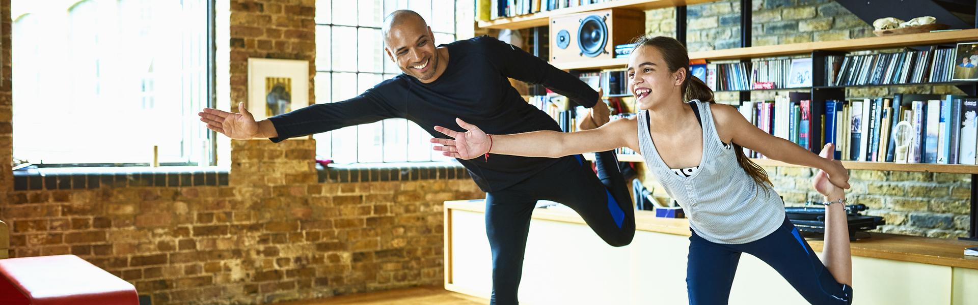 父亲和女儿在家里做瑜伽拉伸运动。
