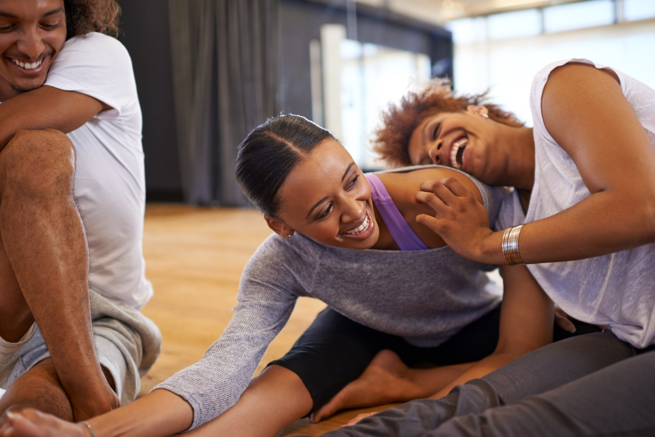 Shot of three happy young women dancers stretching on the floor
